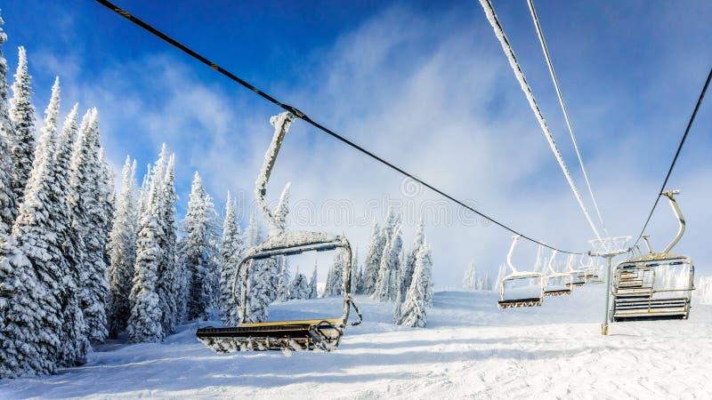 Leeren Sie sich, schneien Sie und gefrieren Sie bedeckte Skiaufzugstühle stockbild
