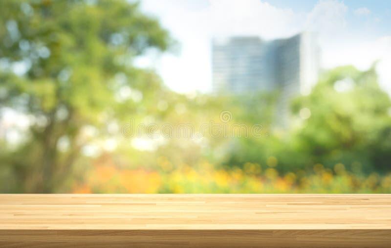 Leeren Sie sich von der hölzernen Tischplatte auf Unschärfe des frischen grünen Gartens mit Stadtstadthintergründen stockbild