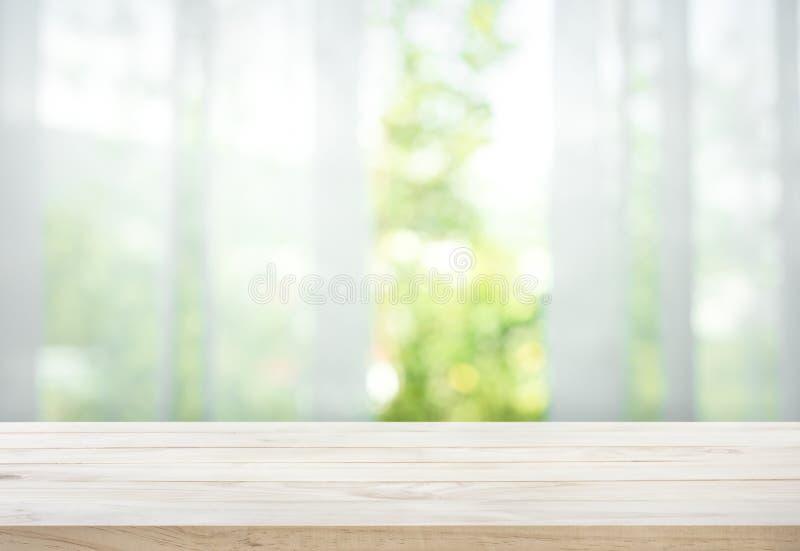 Leeren Sie sich von der hölzernen Tischplatte auf Unschärfe des Vorhangs mit Fensteransichtgrün vom Baumgarten lizenzfreie stockfotografie
