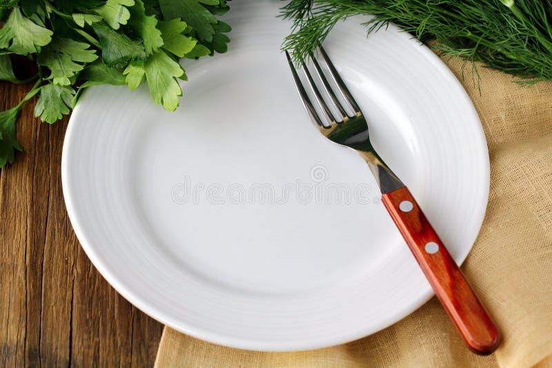 Leeren Sie weiße Platte mit Gabel auf hölzerner Tabelle stockfoto