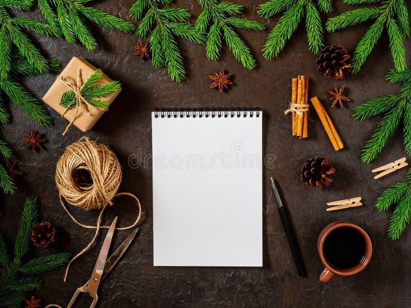 Leeren Sie weißes Notizbuch und Stift auf dunkles Schwarzes Weihnachtshintergrund von Tannenzweigen, Kegel, Geschenke Buchstabe,  lizenzfreie stockfotografie
