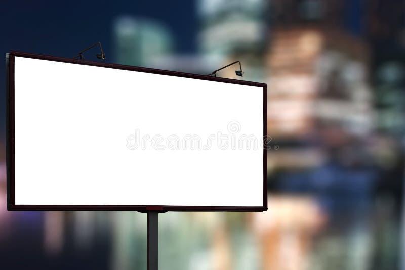 Leerer Anschlagtafelspott oben gegen Nachtgeschäfts-Stadtzentrumhintergrund lizenzfreie stockfotos