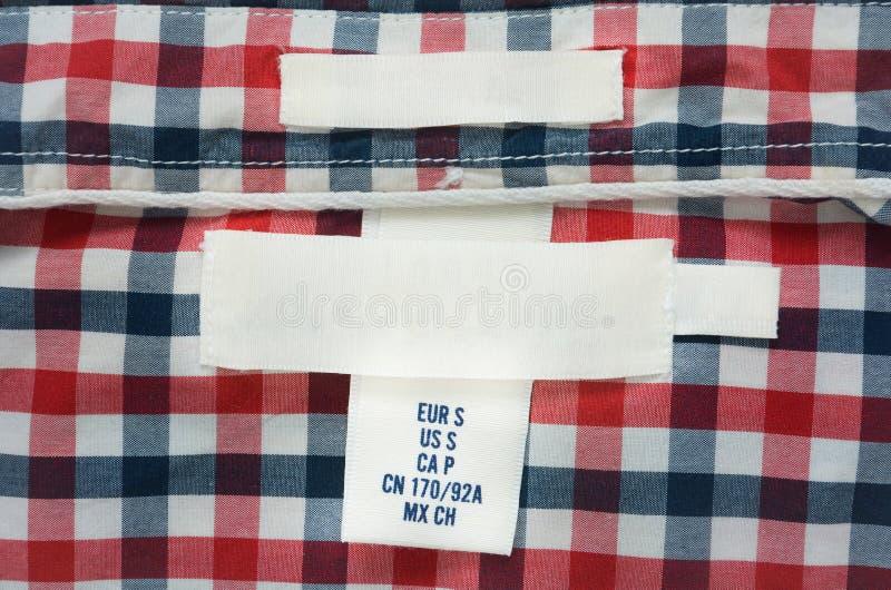 Leerer Beschaffenheitsaufkleber auf rotem, blauem und weißem kariertem Hemd stockfoto
