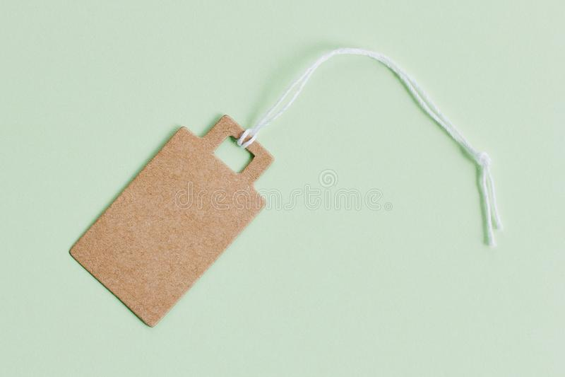 Leerer brauner Papp-Preis, Verkaufstag, Geschenktag, Adressen-Etikett auf grünem Pastellhintergrund lizenzfreie stockfotos
