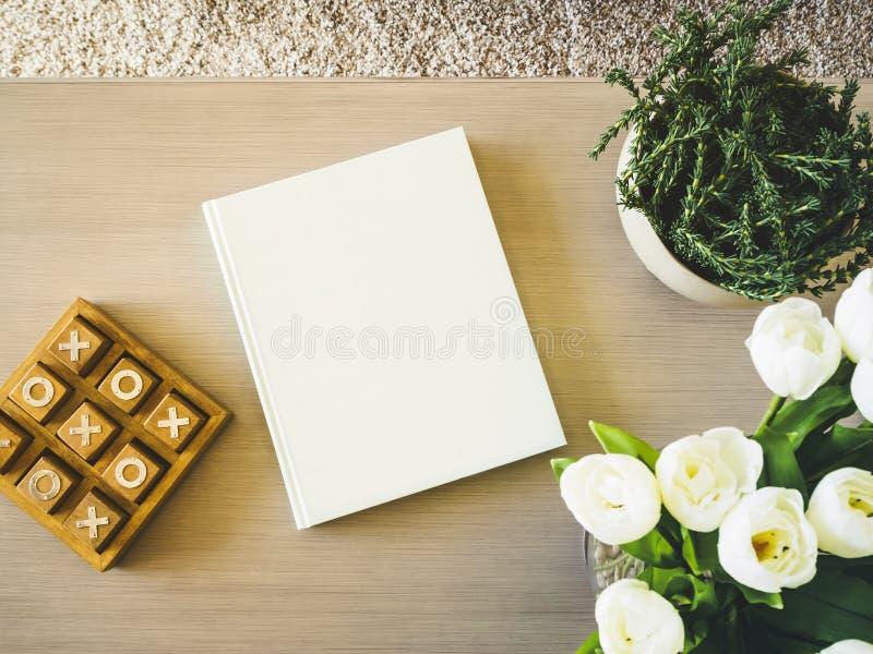 Leerer Bucheinband auf Tabelle mit Blumenanlageninneneinrichtung stockbilder