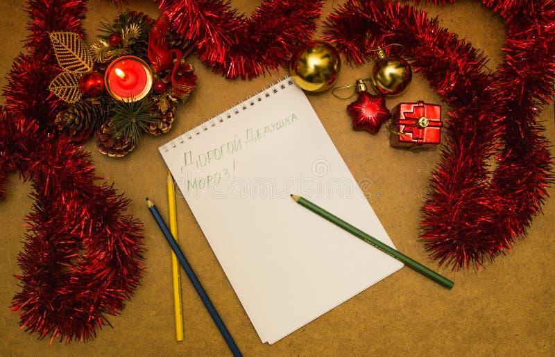 Leerer Buchstabe zu Santa Claus mit einer Kerze, einem Lametta und Weihnachtsspielwaren stockfoto