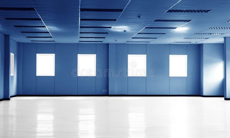 Leerer dunkelblauer Büroraumraum im Bürogebäude oder in der Fabrik mit Fenstern und Kopienraum stockfotografie