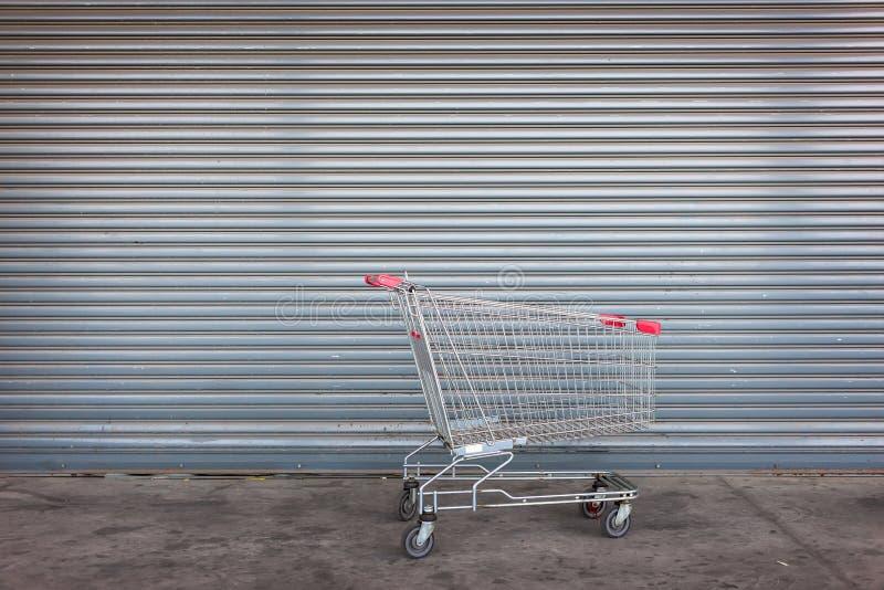 Leerer Einkaufswagen auf naher Ladent?r lizenzfreie stockbilder