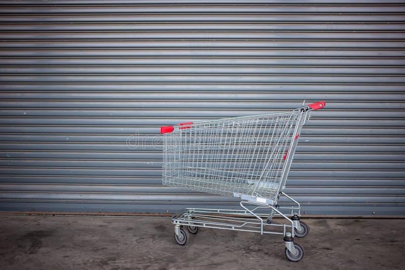 Leerer Einkaufswagen auf naher Ladent?r lizenzfreie stockfotografie