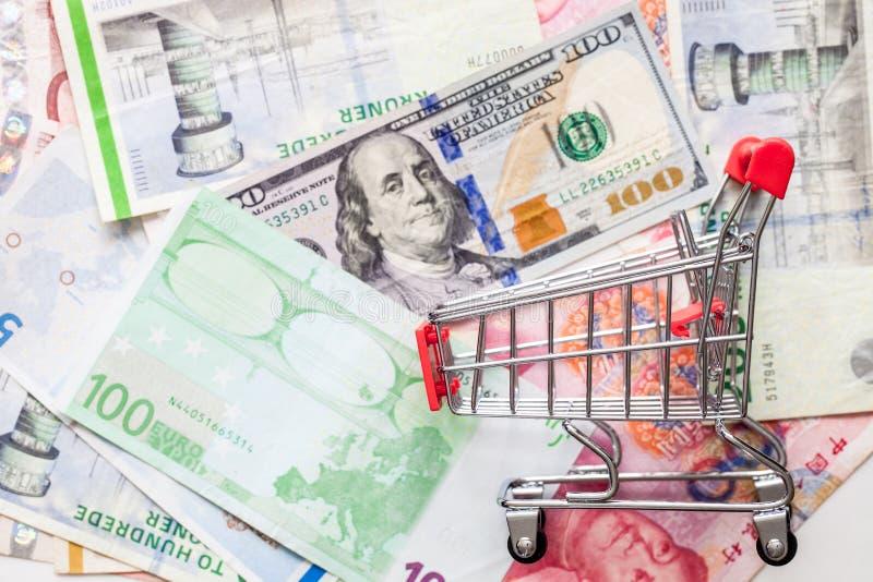 Leerer Einkaufswagen auf verschiedenes Konzept der globalen Wirtschaft der Banknoten mit Kopienraum lizenzfreies stockfoto