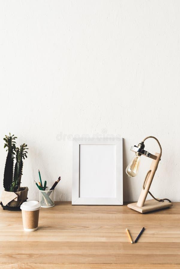 leerer Fotorahmen, Anlage im Blumentopf, Tischlampe und Kaffee zum Mitnehmen stockbild