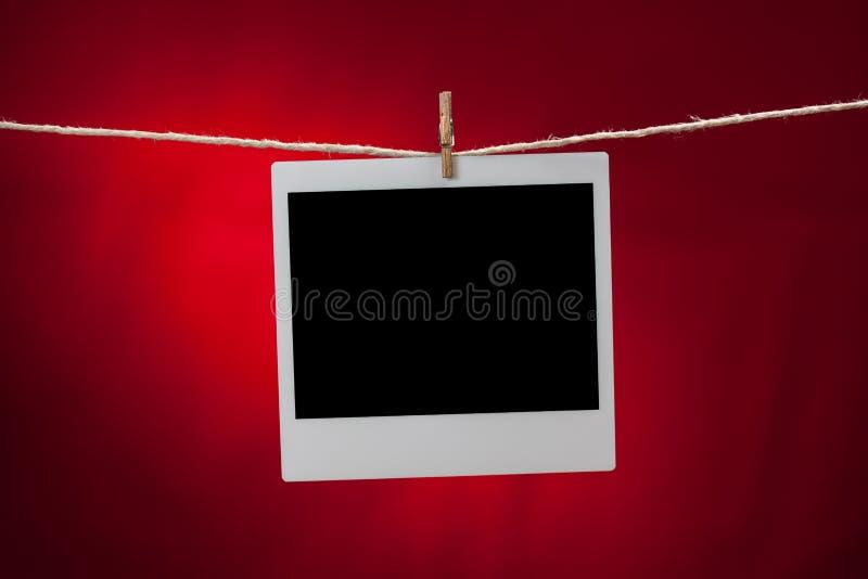 Leerer Fotorahmen auf rotem Hintergrund lizenzfreie stockbilder