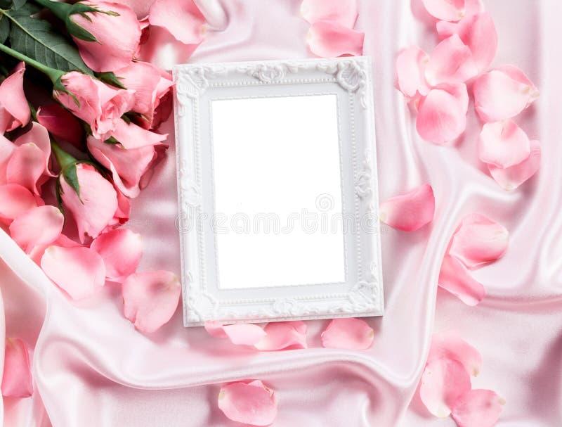 Leerer Fotorahmen mit einem süßen rosa Rosenblumenblatt des Blumenstraußes auf weichem rosa Seidengewebe, Romance und Liebe kardi lizenzfreie stockfotos