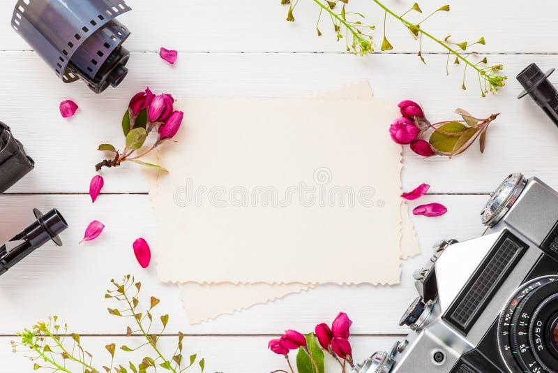 Leerer Fotorahmen, Retro- Kamera, Fotofilmstreifen und Blumen lizenzfreie stockfotos