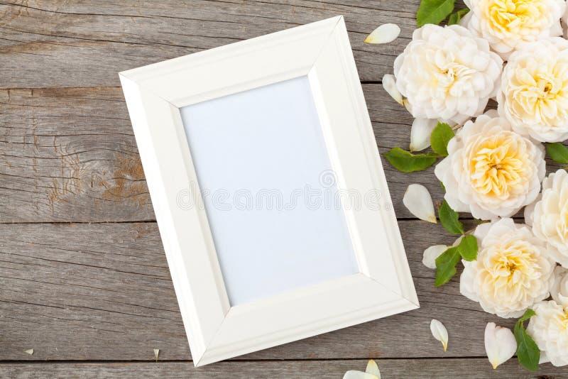 Leerer Fotorahmen und weiße Rosen lizenzfreie stockfotos
