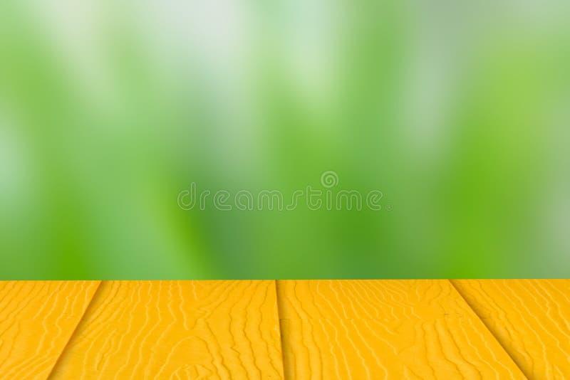 Leerer gelber Holztisch auf undeutlichem Hintergrund der grünen Natur, Kopienraum für Ihren Text Montageproduktanzeige lizenzfreie stockbilder