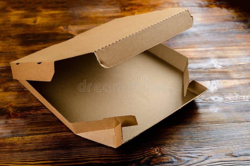 Leerer Handwerkspapppizzakasten auf Holztisch stockfotos