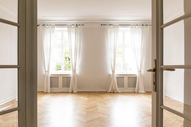 Leerer heller Wohnzimmerinnenraum mit drapiert an den Fenstern und fleht an stockbilder