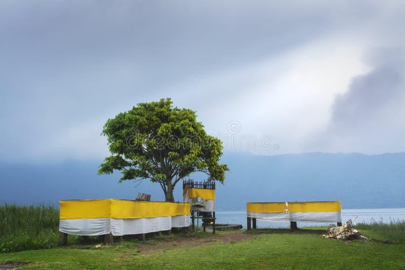 Leerer Hindu-Bali-Tempel auf Seeufer nach dem religiösen Zeremoniell, das mit Sonnenlicht von Misty Morning Cloudy Sky Shinning a lizenzfreie stockbilder