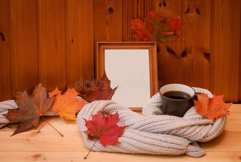 Leerer Holzrahmen, Becher Kaffee eingewickelt im grauen woolen Schal und bunter Herbstlaub auf Holztisch lizenzfreie stockfotos