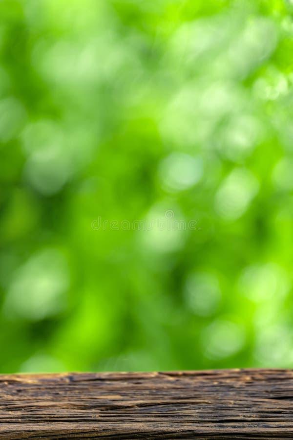 Leerer Holztisch über grünem Hintergrund der Unschärfe, natürliche Szene mit copyscape stockbilder