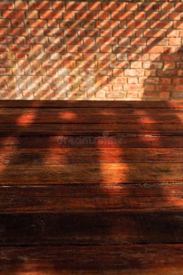 Leerer Holztisch mit Backsteinmauer-und Sonnenlicht-Schatten stockbilder