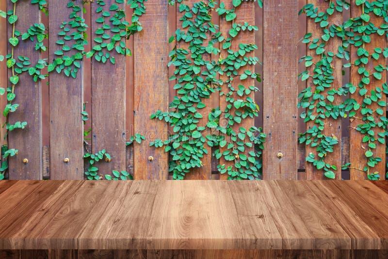 Leerer Holztisch mit Holz und Rebe ummauern Hintergrund lizenzfreie stockfotografie