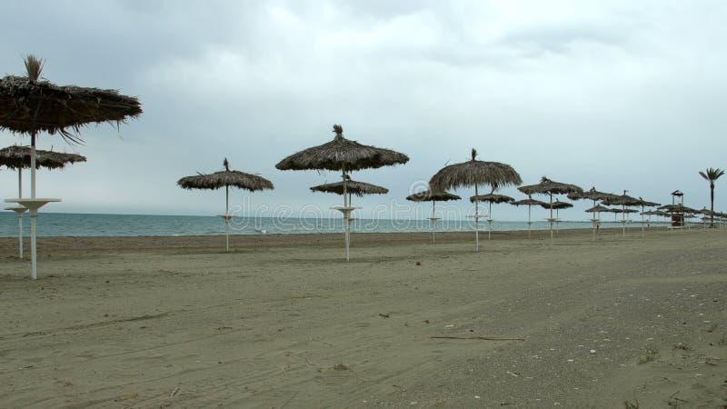 Leerer Küstenstrand, kühles Wetter am populären Sommerurlaubsort während der Nebensaison stockbilder