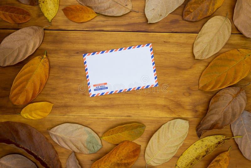 Leerer Luftpostumschlag auf hölzernem Hintergrund mit orange Blatt Leerer Umschlag im Herbstsaisondekor lizenzfreie stockfotos