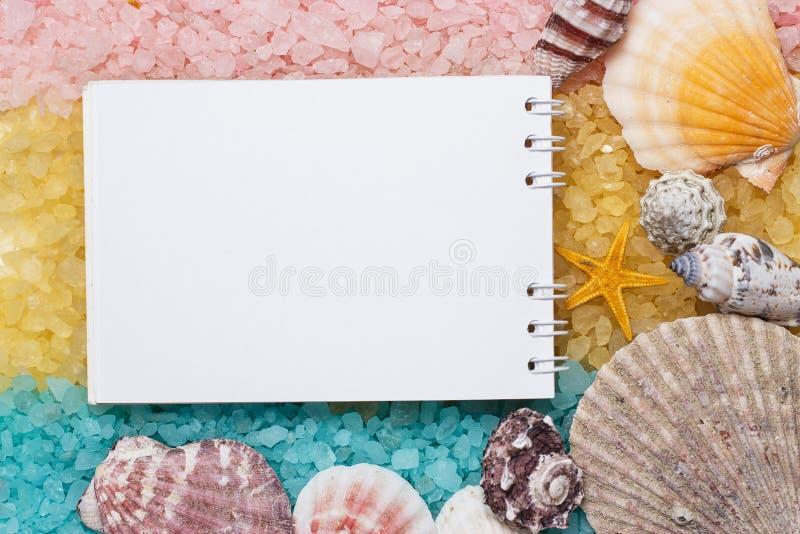 Leerer Notizblock über blauem gelbem rosa Badesalze stockbild