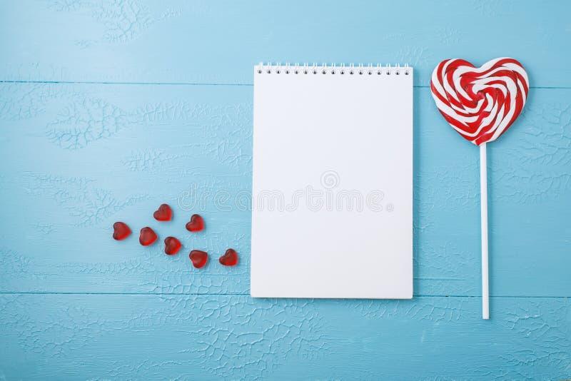 Leerer Notizblock für Text, Lutscher, Herz Blaue Tabelle lizenzfreie stockfotos