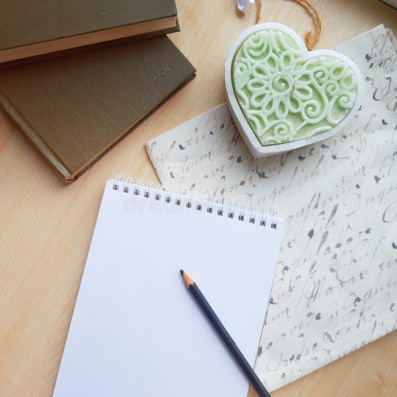 Leerer Notizblock, Kerzenform des Herzens und B?cher auf Holztisch lizenzfreie stockbilder