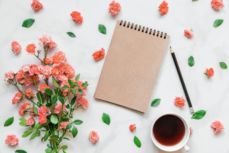 Leerer Notizblock mit Blumenstrauß von rosafarbenen Blumen in lebender korallenroter Farbe und in der Kaffeetasse Universalschabl stockbilder