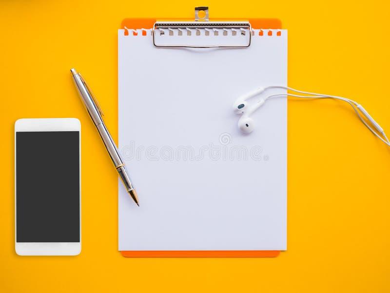 Leerer Notizblock, Stift, Kopfhörer und Smartphone auf Gelb stockfotos
