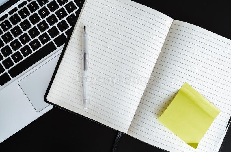 Leerer offener Notizblock mit gelber klebriger Anmerkung nahe bei Laptop-Computer lizenzfreie stockfotografie