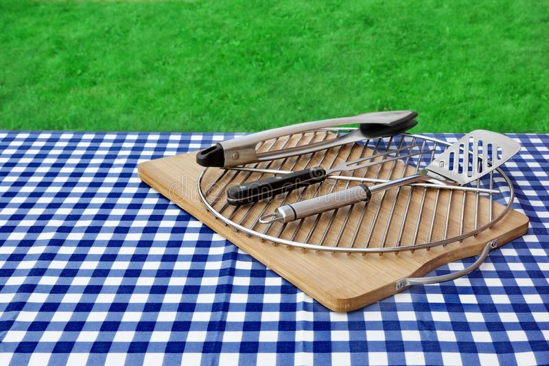 Leerer Picknicktisch, karierte Tischdecke, Gitter, BBQ-Grill-Werkzeuge stockbilder