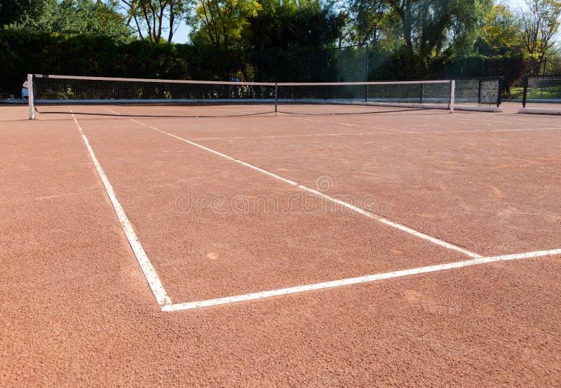 Leerer privater Tennisplatz des orange braunen Sandes bereit zum Spiel lizenzfreie stockfotografie
