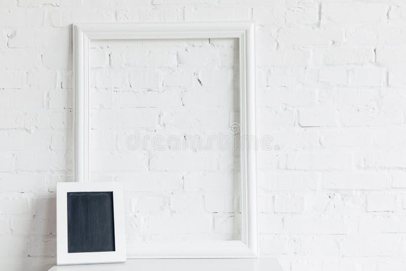 Leerer Rahmen und kleine Tafel vor weißer Backsteinmauer stockfotos