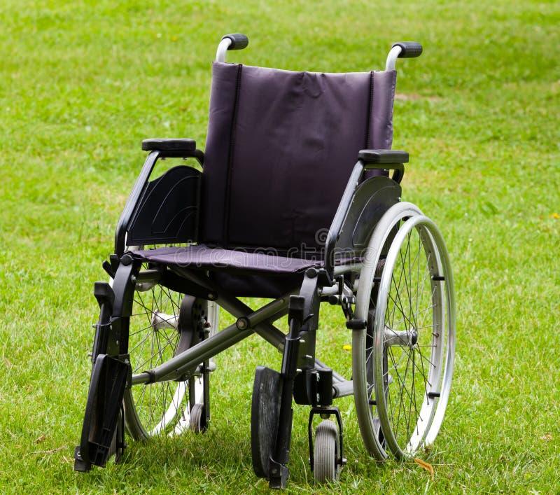 Leerer Rollstuhl auf Rasenfläche stockfotos