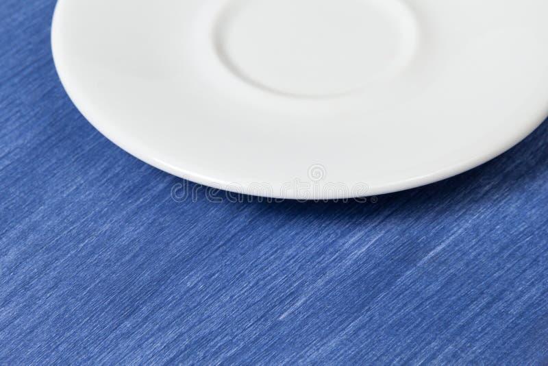 Leerer Saucer auf blauer hölzerner Oberfläche stockbilder