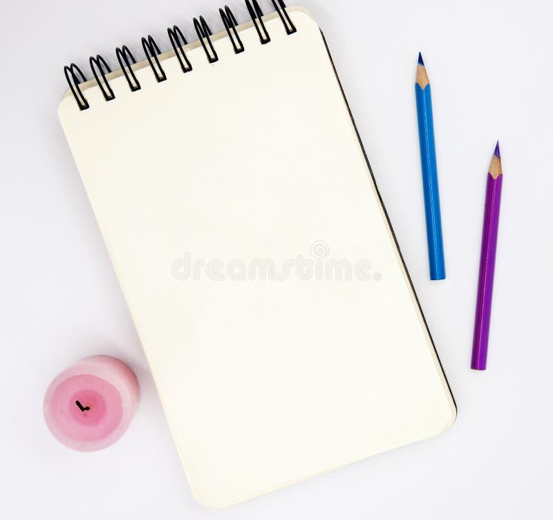 Leerer Sketchbook, rosa violette Bleistifte, rosa Kerze auf weißem Hintergrund Künstlerisches Tischplatteansichtfoto lizenzfreie stockfotos