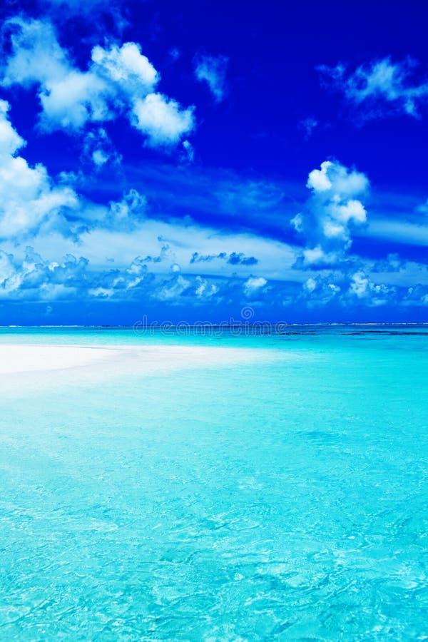 Leerer Strand mit blauem Himmel und vibrierendem Ozean stockfotografie