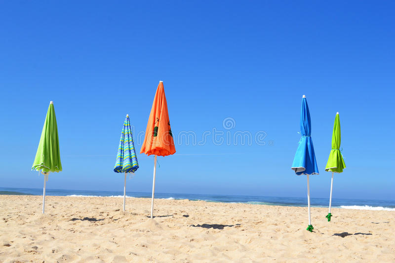 Leerer Strand mit geschlossenen Sonnenschirmen lizenzfreie stockfotos