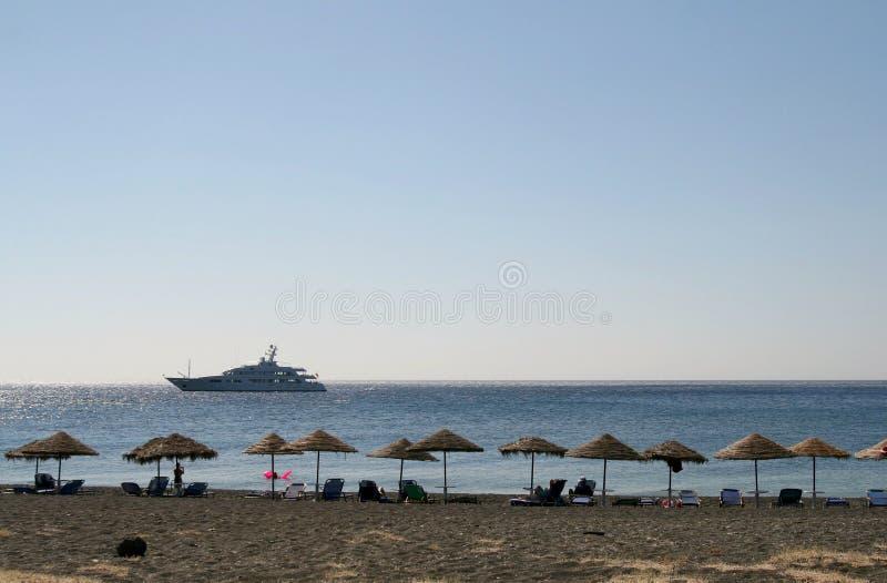 Leerer Strand mit Sonnefarbtönen und Stühlen, Griechenland lizenzfreies stockbild