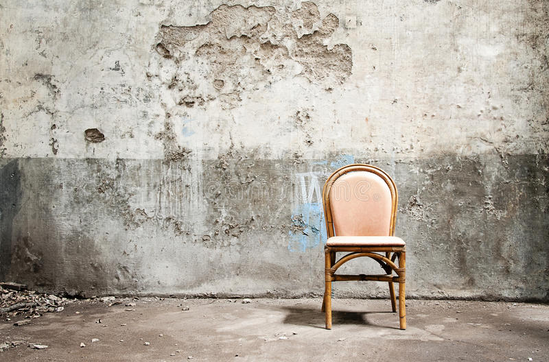 Leerer Stuhl und grungy Wand lizenzfreie stockbilder