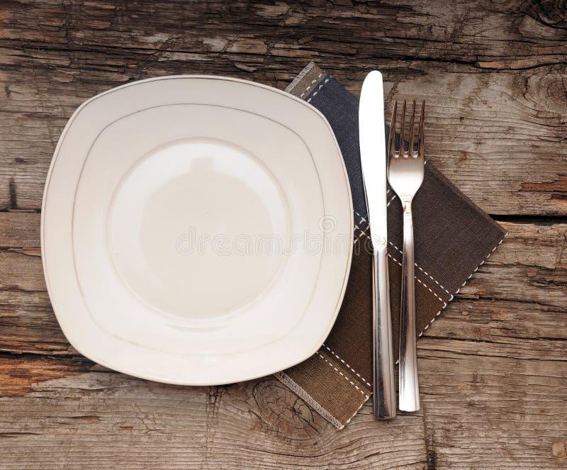 Leerer Teller, Messer und Gabel und braune Serviette stockfotos