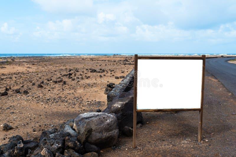Leerer weißer Wegweiser, Anschlagtafel, Informationsbrett, Zeichen am Straßenrand in verlassener Küstenlandschaft mit Ozean im Hi stockbilder