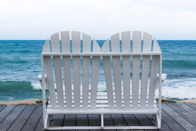Leerer weißer hölzerner Strandstuhl auf Promenade stockfoto