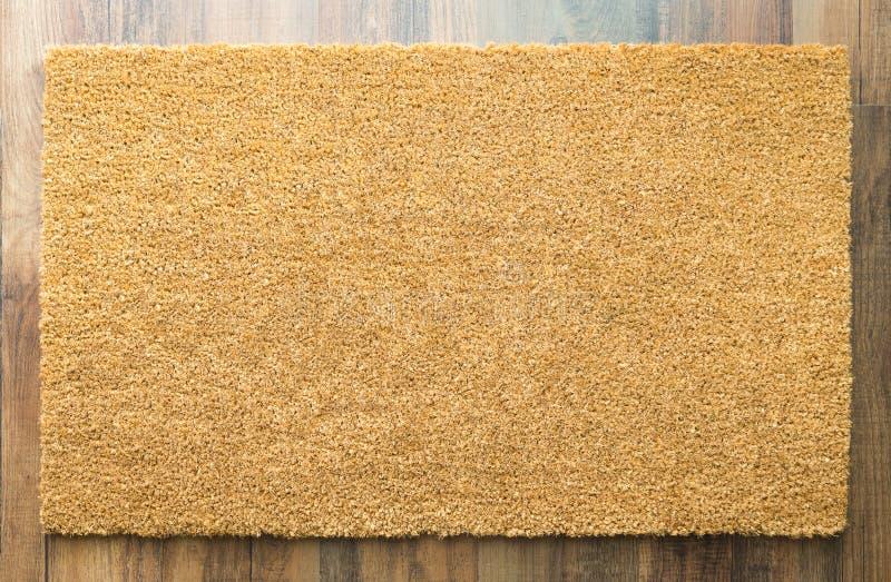 Leerer willkommener Mat On Wood Floor lizenzfreie stockbilder