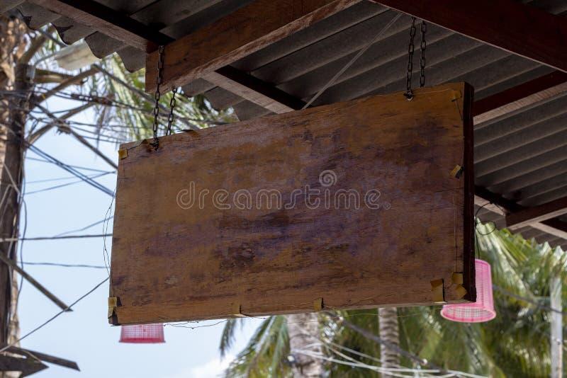 Leerer Zeichenfall des hölzernen Brettes unter Dach Tropeninselcafé oder Hotelzeichenmodell Hölzernes Brett mit Palmblatt stockfoto